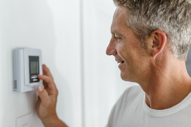 Man turning down thermostat