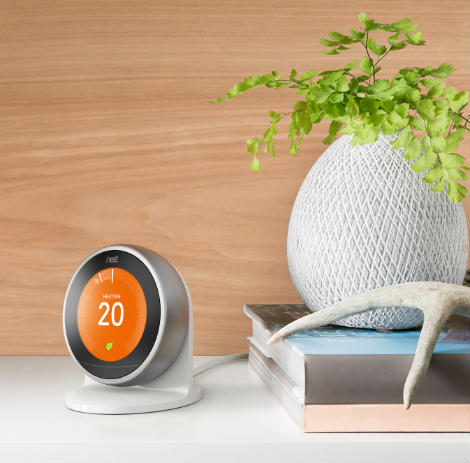 A Nest Learning Thermostat on a stand within a home